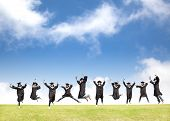 stock photo of grassland  - College students celebrate graduation and happy jump with blue sky - JPG