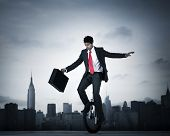 stock photo of unicycle  - Businessman Taking a Risk on Unicycle in New York City - JPG