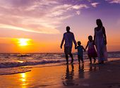 stock photo of children beach  - Family Walking on The Beach at Sunset - JPG