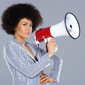 Stylish beautiful young African American woman with curly afro hair and a megaphone with a jaunty at