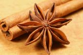 stock photo of ouzo  - Anise star and cinnamon stick on wooden background - JPG