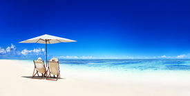 stock photo of canopy  - Couple Relaxing in Deck Chairs on Tropical Beach - JPG