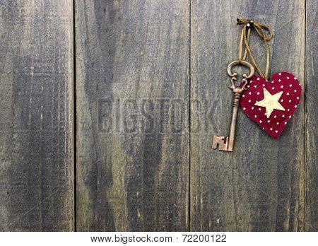 Star heart and antique bronze skeleton key hanging on rustic wood door