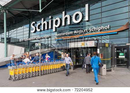 Airport Entrance With Passing Travellers At The Airport Of Amsterdam