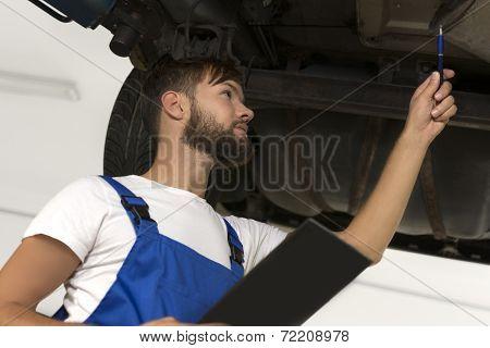 Male Car Mechanic Working Under Car