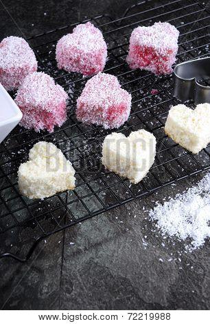 Making Australian Style Pink Heart Shape Small Lamington Cakes On Baking Rack With Strawberry Sauce