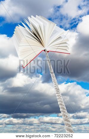 Book Tied On Rope Soars Into Grey Clouds