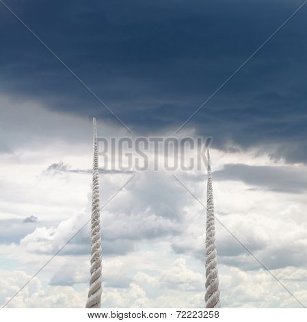 Two Ropes Rise To Sky With Rainy Clouds