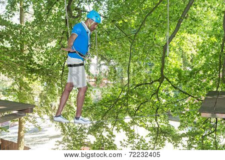 Man Climbing On Tightrope In High Rope Course