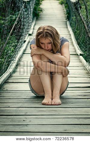 Portrait of a sad girl on the bridge