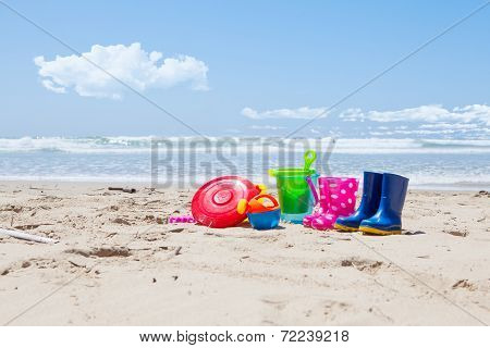 Plastic Toys And Gumboots On The Beach Sand