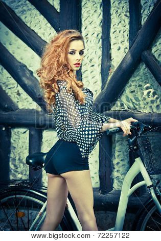 Beautiful girl wearing ultramarine blouse and black sexy shorts in park with bicycle