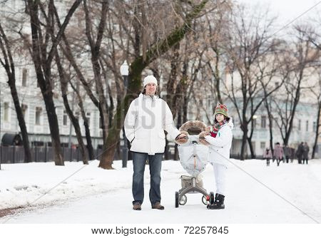 Young Man With A Son And Baby In A Stroller Walking In A Snowy Park