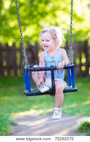 Happy Laughing Toddler Girl enjoying a swing ride