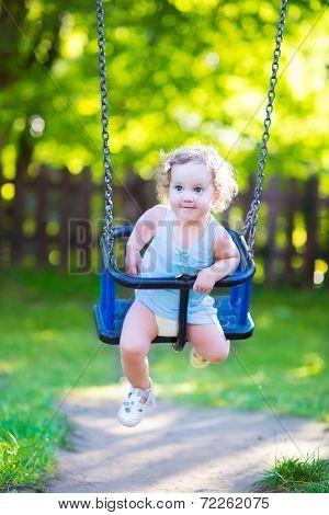 Happy Laughing Toddler Girl enjoying a swing ride