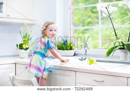 Pretty Toddler Girl washing dishes, cleaning with a sponge and playing with foam in the sink