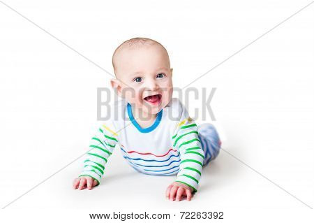 Happy Laughing Baby Boy In A Colorful Shirt Playing On His Tummy, On White Background