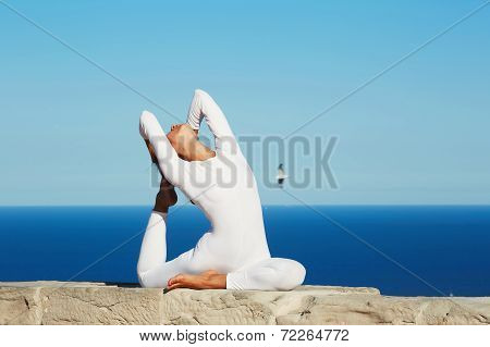 Attractive brunette girl with beautiful body engage yoga at high altitude on beautiful ocean backgro