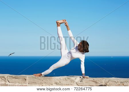 Stretching yoga pose performed by beautiful brunette woman in white clothes, girl engage yoga