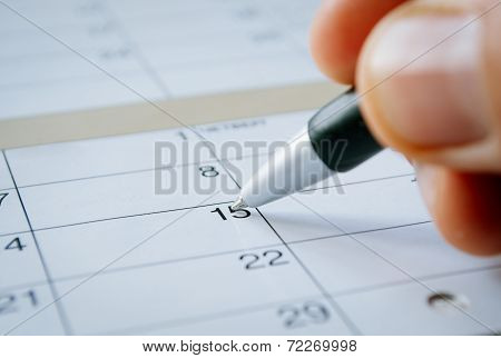 Person Writing On A Calendar Date Of The 15Th