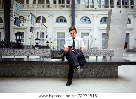Serious businessman sitting on the railway station bench holding his mobile phone in the hand
