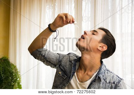 Man Dropping Medicine From Eyedropper Into Mouth