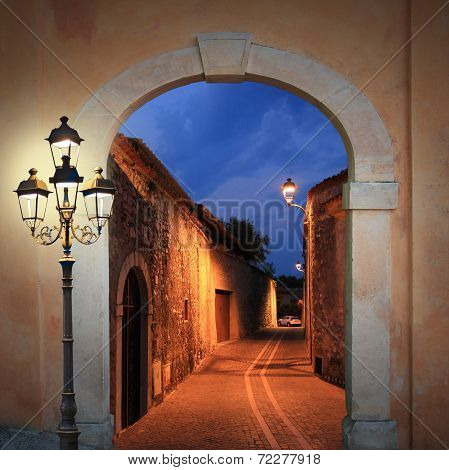 Moody Illuminated Alleyway With Arched Gate And Burning Lantern