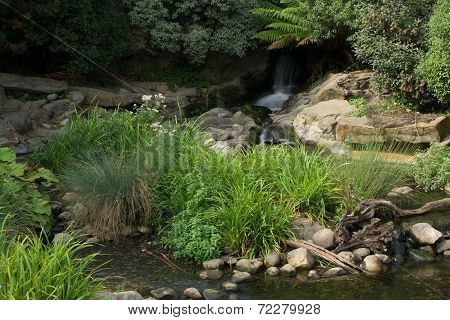 Blurred Waterfall And Rocky Riverbed In Sunshine