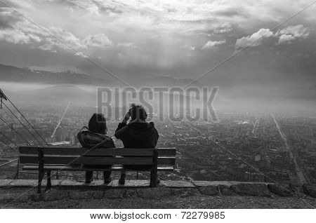 Couple In A Bank Seeing The City And The Sunset