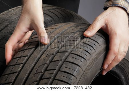 Car service. Wheels and man's hand