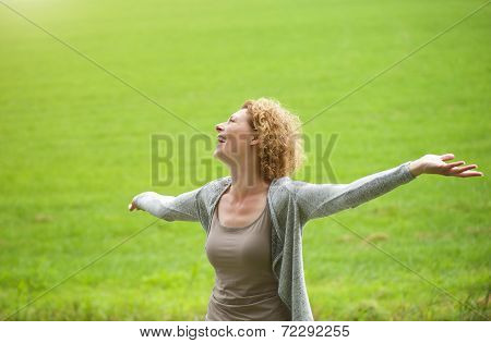 Woman Enjoying The Outdoors With Arms Spread Open