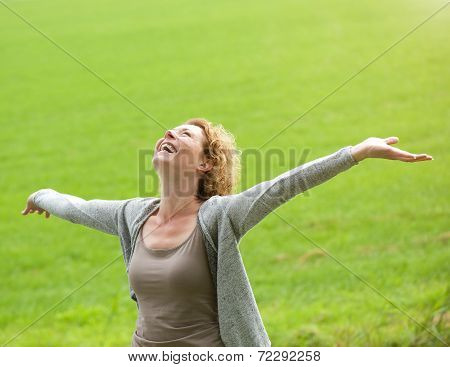 Cheerful Older Woman Smiling With Arms Outstretched