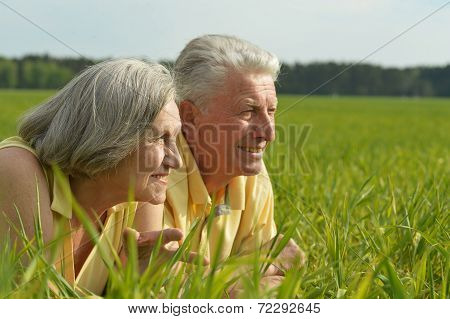 Old couple lying on the field