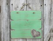 image of wooden fence  - Blank green sign with wooden heart hanging on distressed wood fence - JPG
