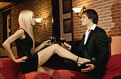 stock photo of court room  - romantic evening date in hotel room happy couple with wine glass sit on red sofa - JPG