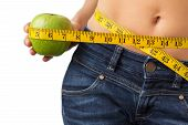 picture of flat stomach  - Woman measuring her waist and holding fresh green apple in hand - JPG