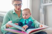 stock photo of lap  - Adorable toddler flipping the pages of a picture book on his moms lap  - JPG