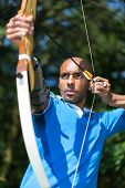 foto of archer  - Bowman or archer aiming at target with bow and arrow - JPG