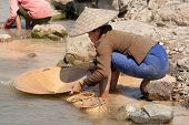 picture of ou  - washing gold in the river woman sieves rock at river Nam Ou in Laos - JPG