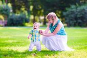 stock photo of little young child children girl toddler  - Beautiful young woman and a happy baby cute little boy playing together in a park the child is learning to walk making his first steps in a sunny summer garden - JPG