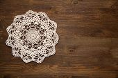 pic of doilies  - Crochet doily over the dark brown wood - JPG