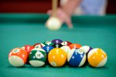 stock photo of concentration man  - Young man playing billiards in the dark billiard club - JPG
