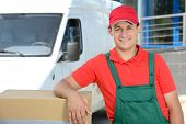 image of moving van  - Smiling young male postal delivery courier man in front of cargo van delivering boxes - JPG