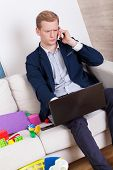 stock photo of toy phone  - Working man talking on phone among child - JPG