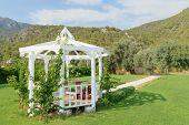 image of pergola  - Image of a garden pergola on a sunny day with mountains and forests in the background against a blue sky with white clouds - JPG