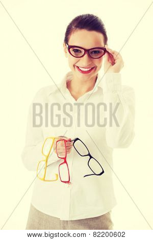 Beautiful woman in eyeglasses holding three different pair of eyeglasses.