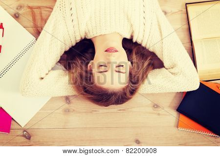 Young beautiful woman lying on the wooden floor with books.