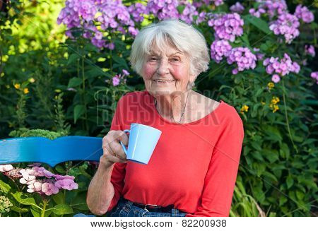 Happy Grandma Having A Coffee At The Garden