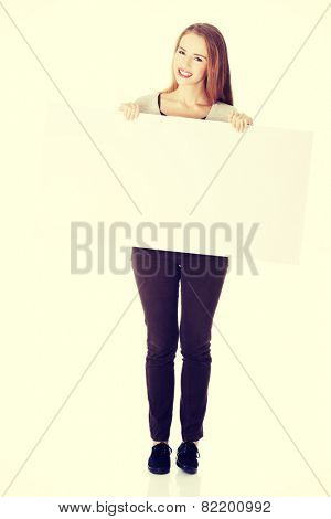 Beautiful casual woman holding copy space and advertising.