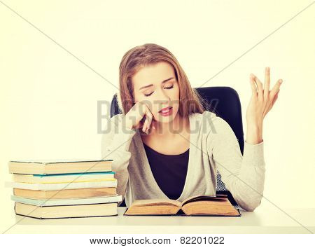 Beautiful resigned student woman with stack of books.